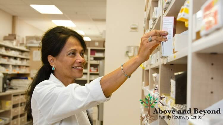 Pharmacist reaching for medication